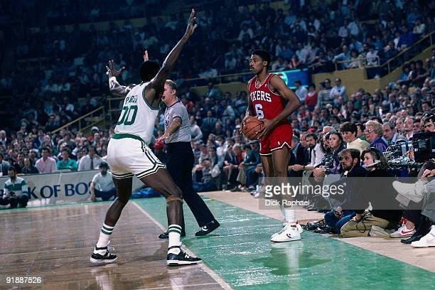 Julius Erving of the Philadelphia 76ers inbounds the ball against Robert Parish of the Boston Celtics during a game played in 1987 at the Boston...