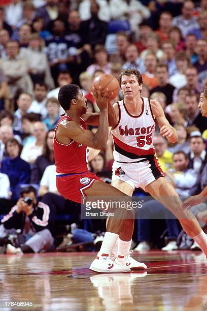 Julius Erving of the Philadelphia 76ers looks to pass against Kiki Vandeweghe of the Portland Trail Blazers during a game played circa 1987 at the...