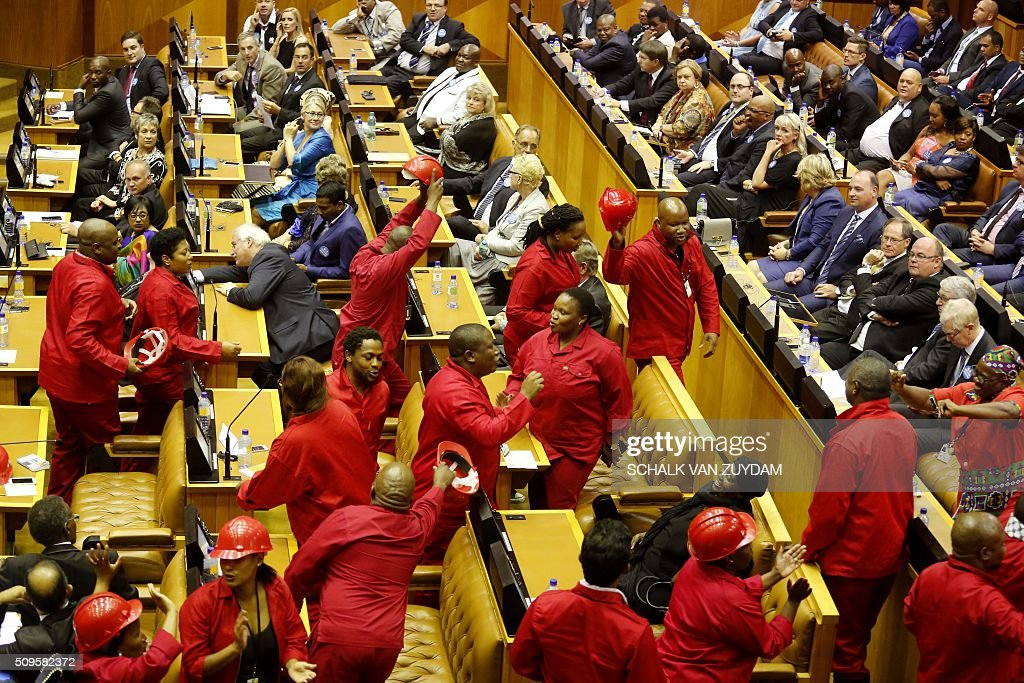 Julius Malema (C)leader of the Economic Freedom Fighters political party leaves the inside of parliament with his members as President Jacob Zuma attempts to give his state of the nation address in Cape Town, South Africa on February 11, 2016. / AFP / POOL / Schalk van Zuydam