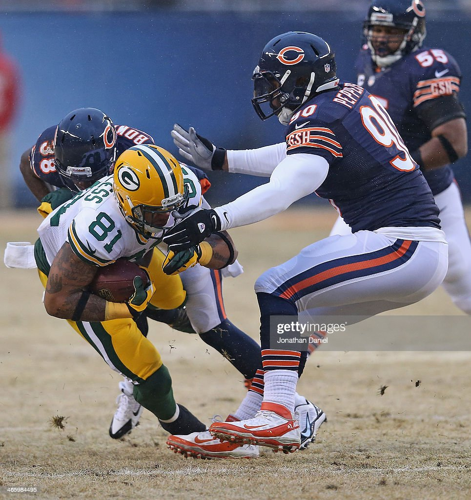 Julius Peppers and Zack Bowman of the Chicago Bears bring down Andrew Quarless of the Green Bay Packers at Soldier Field on December 29 2013 in...