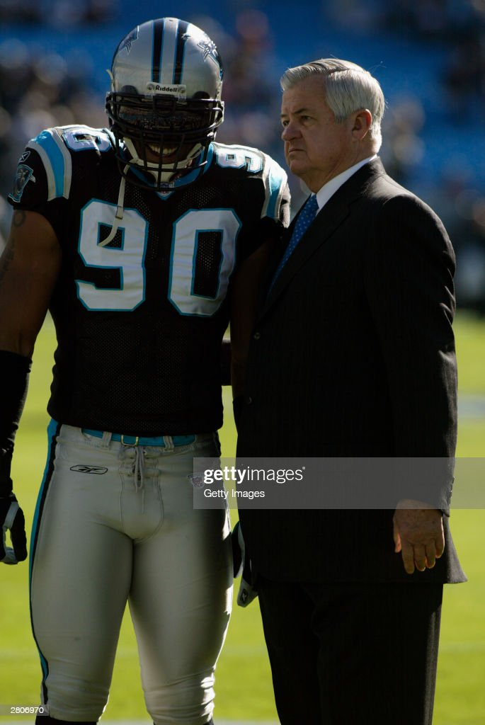 Julius Peppers #90 of the Carolina Panthers stands with owner Jerry Richardson during the game against the Philadelphia Eagles on November 30, 2003 at Ericsson Stadium in Charlotte, North Carolina. The Eagles defeated the Panthers 25-15.