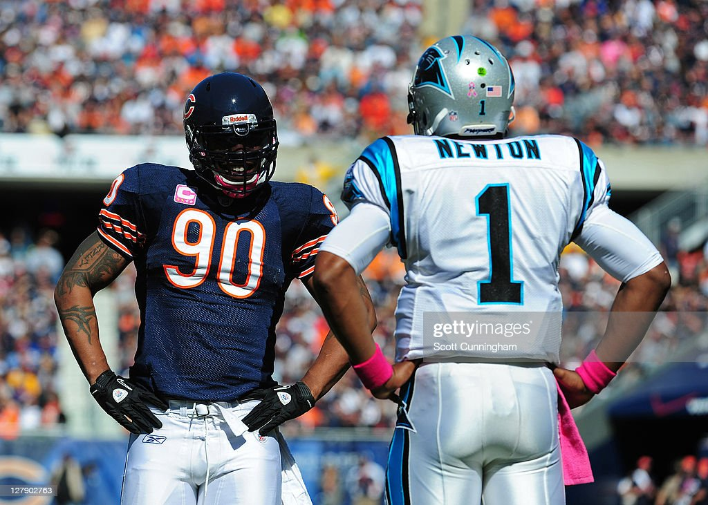 Julius Peppers #90 of the Chicago Bears chats with Cam Newton #1 of the Carolina Panthers during a timeout at Soldier Field on October 2, 2011 in Chicago, Illinois.