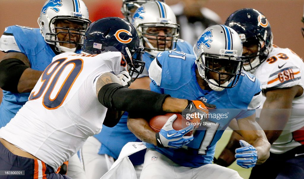 Julius Peppers #90 of the Chicago Bears grabs a hold of Reggie Bush #21 of the Detroit Lions at Ford Field on September 29, 2013 in Detroit, Michigan.