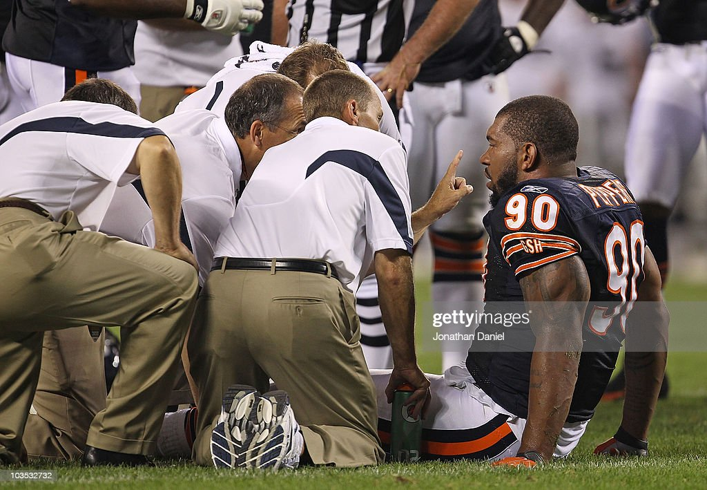 Julius Peppers of the Chicago Bears is attended to by trainers after an injury against the Oakland Raiders during a preseason game at Soldier Field...