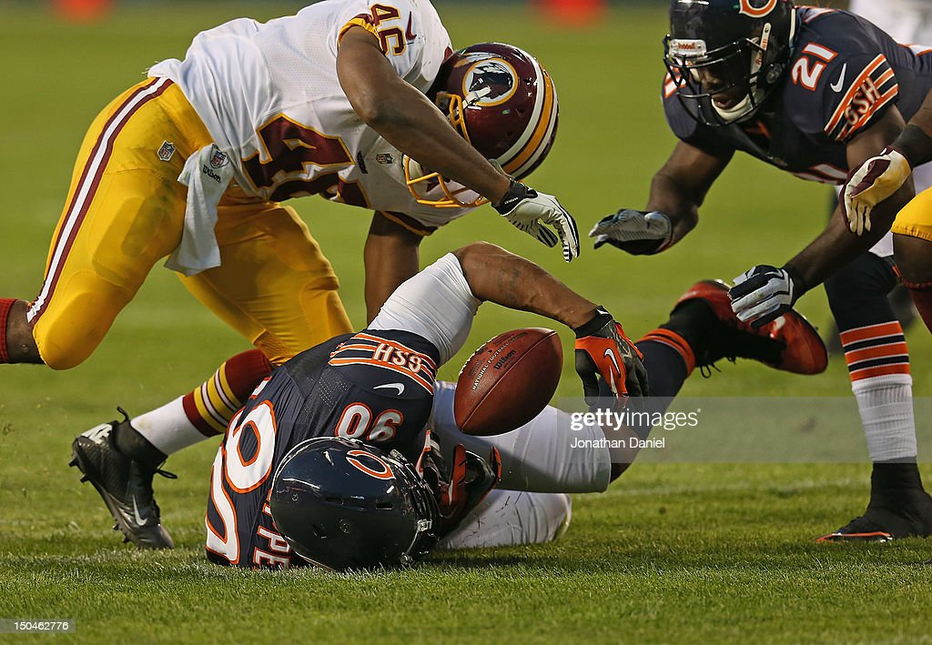 Julius Peppers of the Chicago Bears recovers a fumble as Major Wright and Alfred Morris of the Washington Redskins close in during a preseason game...