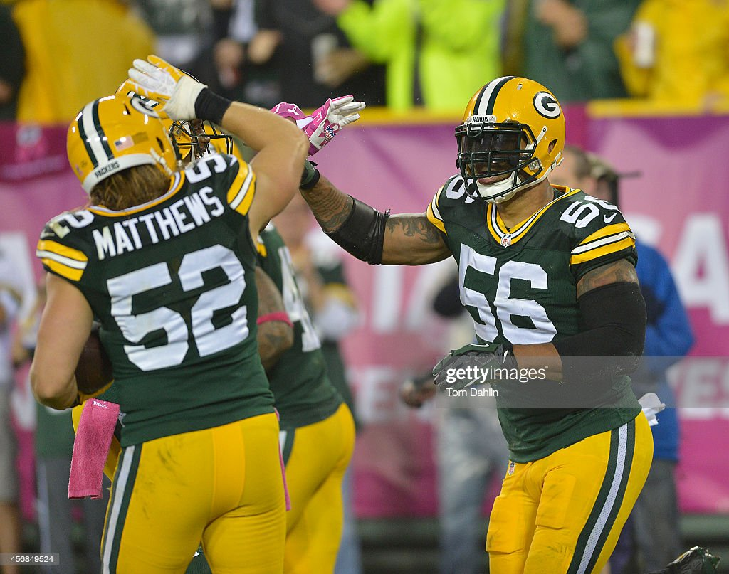 Julius Peppers of the Green Bay Packers celebrates a touchdown with Clay Matthews following an interception during an NFL game against the Minnesota...