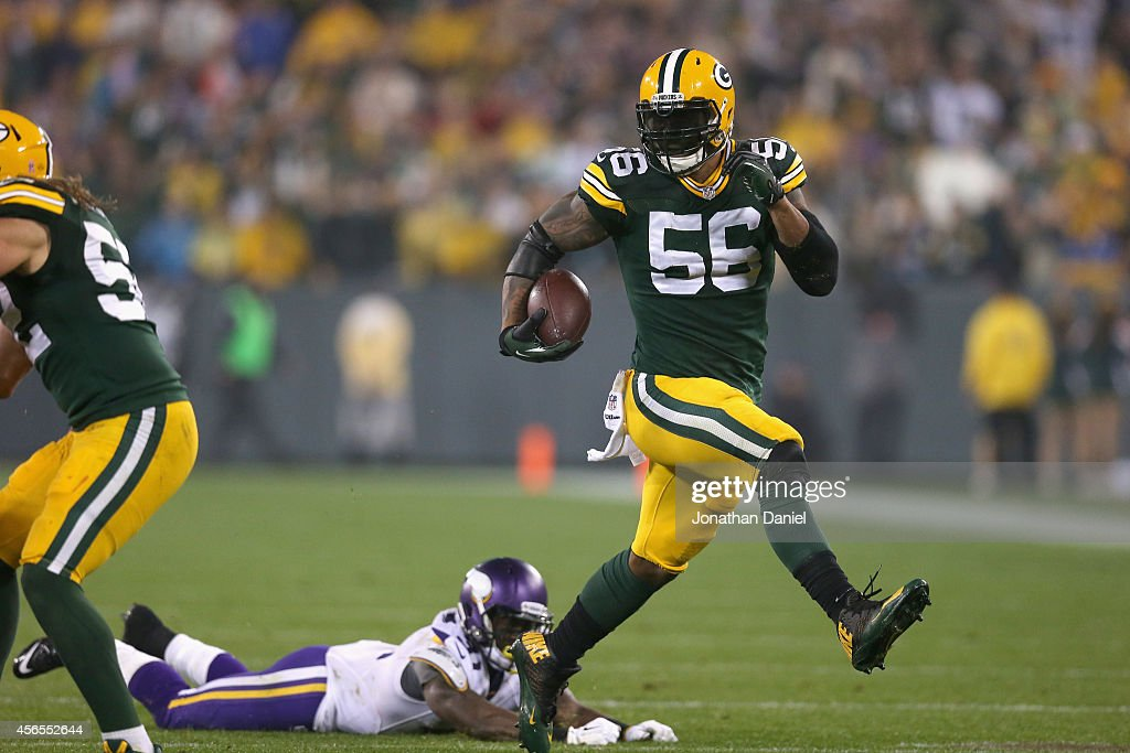 Julius Peppers of the Green Bay Packers runs the ball for 46 yards on an interception to score against the Minnesota Vikings at Lambeau Field on...