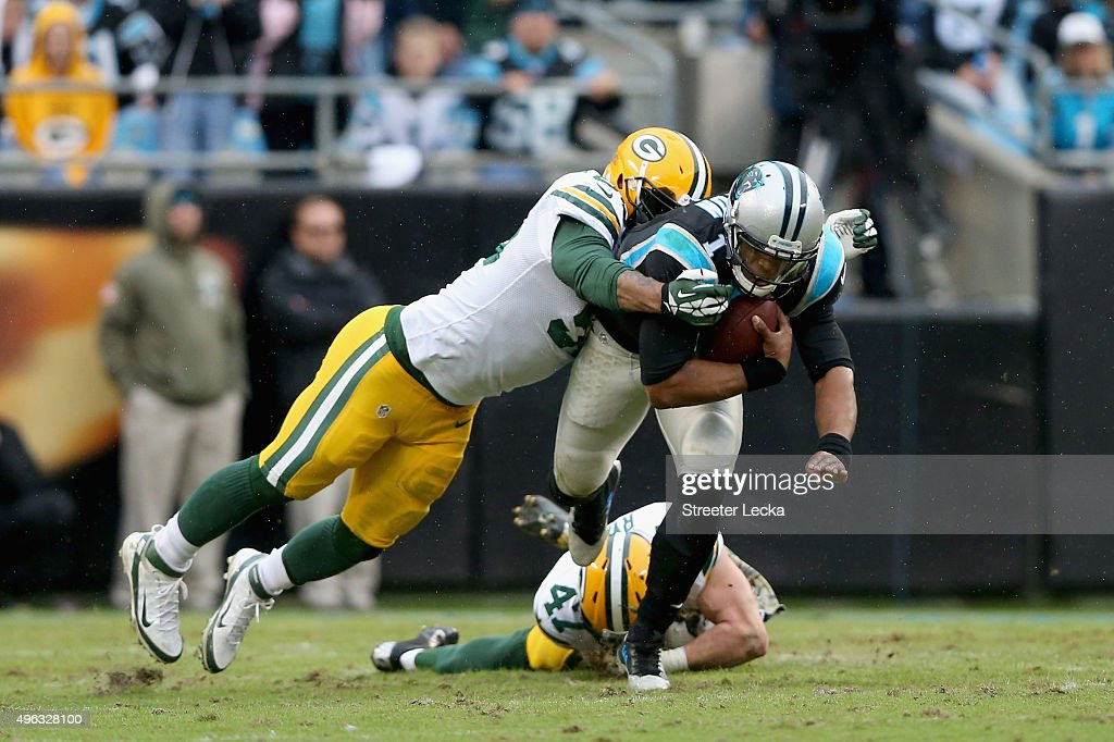 Julius Peppers of the Green Bay Packers tackles Cam Newton of the Carolina Panthers in the 2nd half during their game at Bank of America Stadium on...