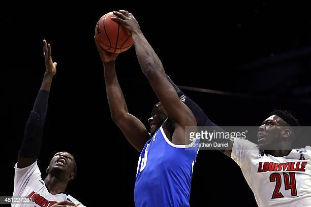 Julius Randle of the Kentucky Wildcats shoots the ball against Mangok Mathiang and Montrezl Harrell of the Louisville Cardinals in the first half...
