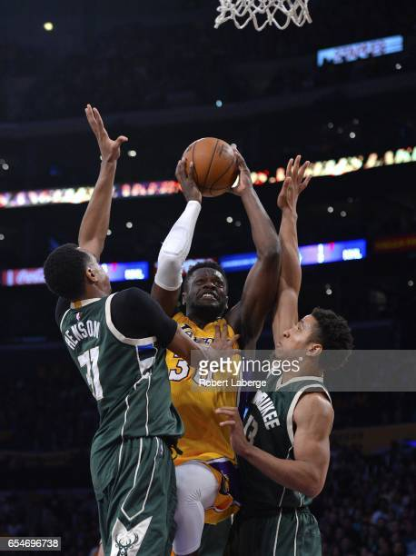 Julius Randle of the Los Angeles Lakers attempts a shot against John Henson Malcolm Brogdon of the Milwaukee Bucks on March 17 2017 at STAPLES Center...