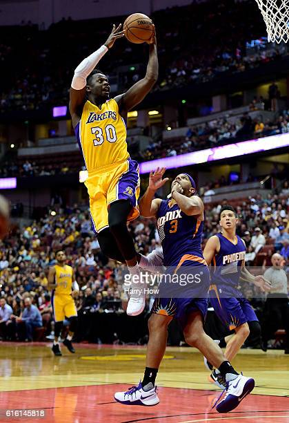 Julius Randle of the Los Angeles Lakers scores on a layup past Jared Dudley of the Phoenix Suns during a preseason game at Honda Center on October 21...