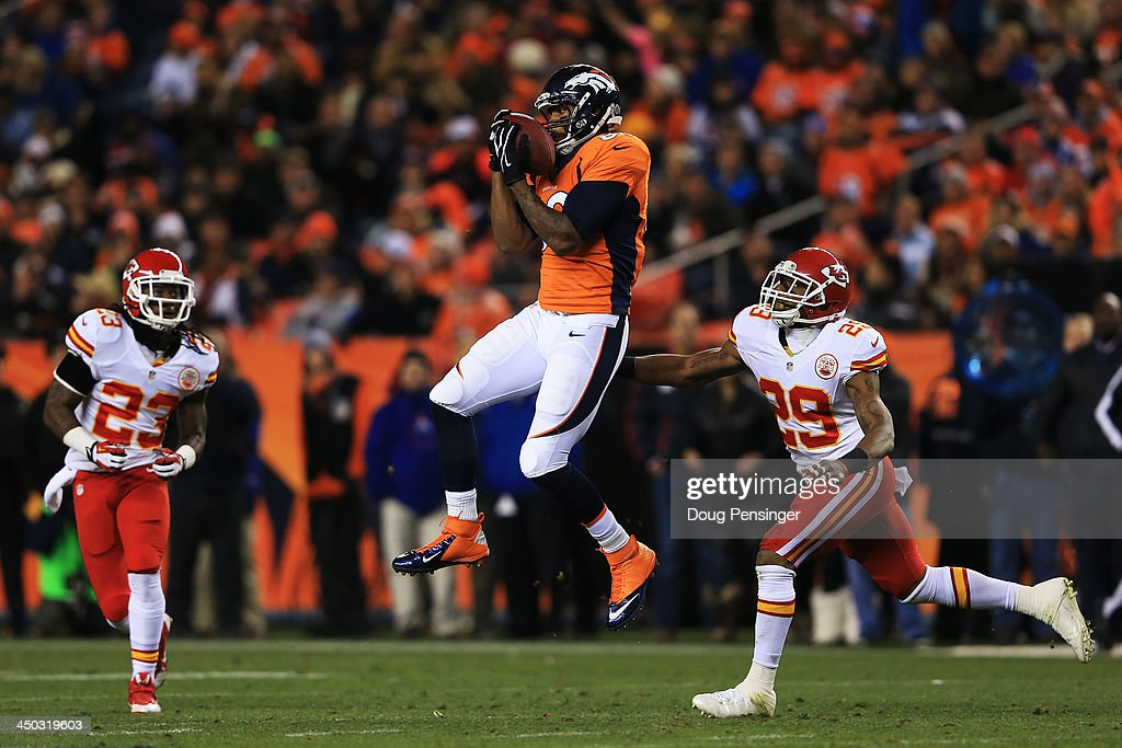 Julius Thomas #80 of the Denver Broncos completes a first down pass reception against the defense of Eric Berry #29 and Kendrick Lewis #23 of the Kansas City Chiefs in the first half at Sports Authority Field at Mile High on November 17, 2013 in Denver, Colorado.