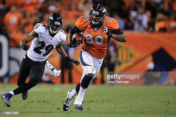 Julius Thomas of the Denver Broncos runs by Michael Huff of the Baltimore Ravens before running in for a 24yard touchdown in the second quarter...