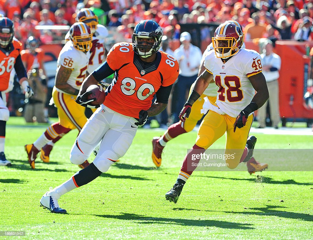 Julius Thomas #80 of the Denver Broncos runs with a catch against Jose Gumbs #48 of the Washington Redskins at Sports Authority Field on October 27, 2013 in Denver, Colorado.