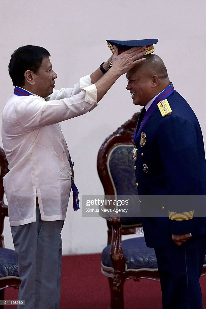 CITY, July 1, 2016-- Philippine President Rodrigo Duterte, left, puts a new hat on National Police Chief Ronald dela Rosa during Ronald dela Rosa's assumption of command ceremony in Quezon City July 1, 2016.