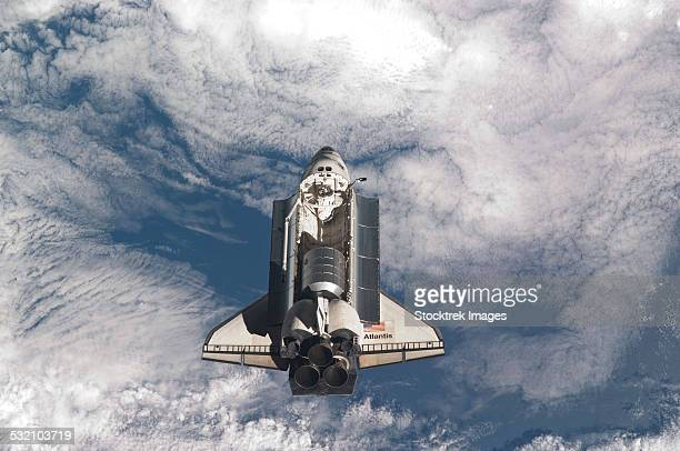 July 10, 2011 - Space shuttle Atlantis backdropped by a cloud covered Earth.