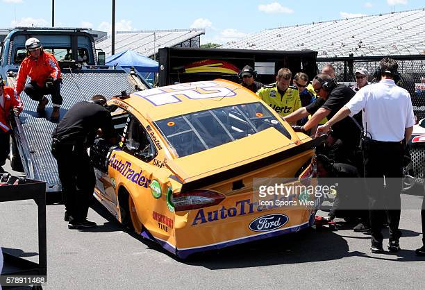 Joey Logano's crew removes his car from the flat bed after he hit the wall in turn 2 during practice for the Sprint Cup Series Camping World RV Sales...