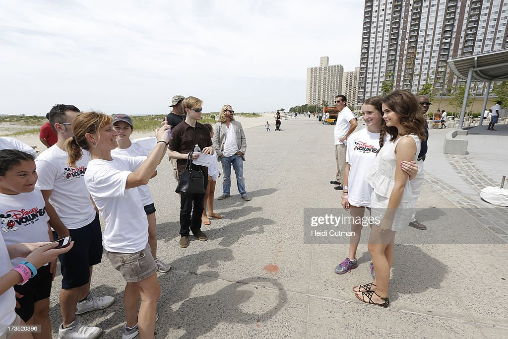 MOVIE - July 14, 2013 - Ross Lynch and Maia Mitchell, starring in the highly anticipated Disney Channel Original Movie, TEEN BEACH MOVIE, pitch in with volunteers from Verizon, Disney and NYC Partnership for Parks, to clean up Rockaway Beach in Queens, NY, that was devastated by Superstorm Sandy. (Photo by Heidi Gutman/Disney Channel via Getty Images) MAIA MITCHELL, VOLUNTEERS