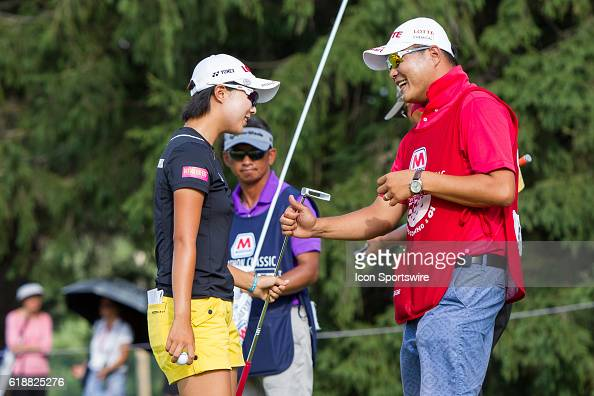 Hyo Joo Kim of South Korea gives her putter to her caddie on the No 9 green at the conclusion of her first round of the LPGA Marathon Classic...