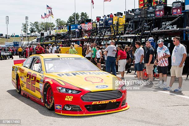 Fans watch from a busy garage as NASCAR Sprint Cup driver Joey Logano driver of the Shell Pennzoil Ford heads back to the track during Friday's first...
