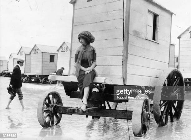 A woman perches on the edge of a bathing machine parked in shallow sea on Ostend beach