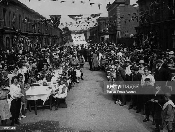 Crowds sitting down at long tables at a street party to celebrate the end of the Great War
