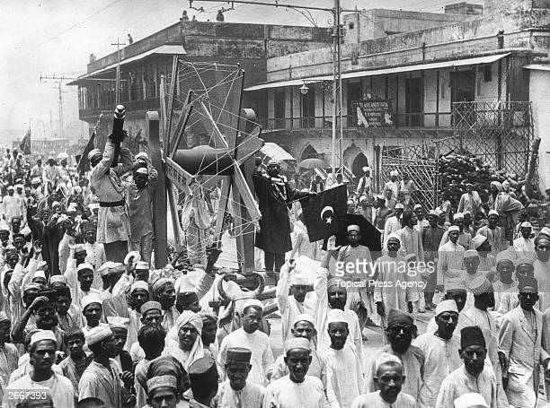 Gandhi Day paraders in Delhi flying the emblem of Islam Water buffalo are pulling a float on which is a large symbolic spinning wheel which is often...