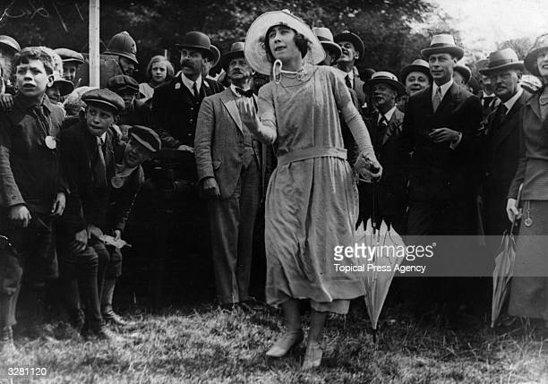 Queen Elizabeth Queen Consort to King George VI trying her hand at the cocunut shy at a fair in Loughton East London