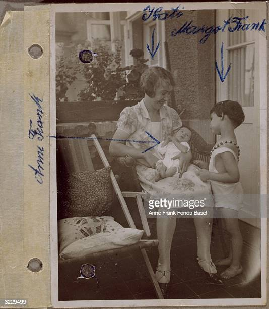 EXCLUSIVE A page from Anne Frank's photo album containing a photograph of Kathi the family's domestic servant holding Anne Frank on her lap with...