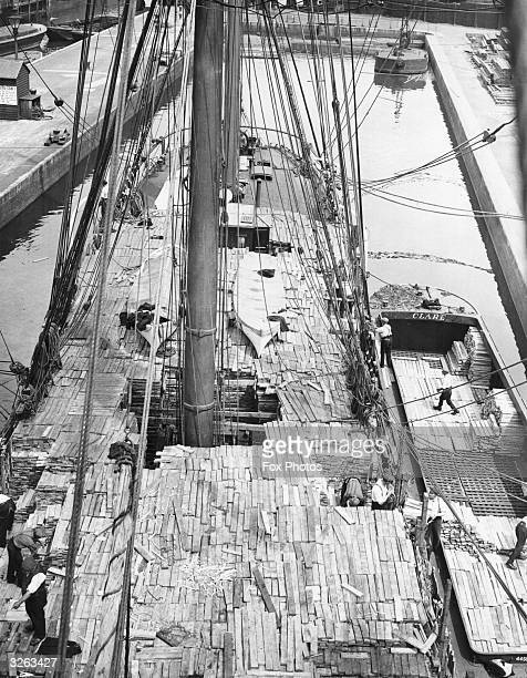 An aerial view of the immense timber cargo being unloaded to barges from the Finnish barque 'Plus' that has recently arrived at the Surrey commercial...