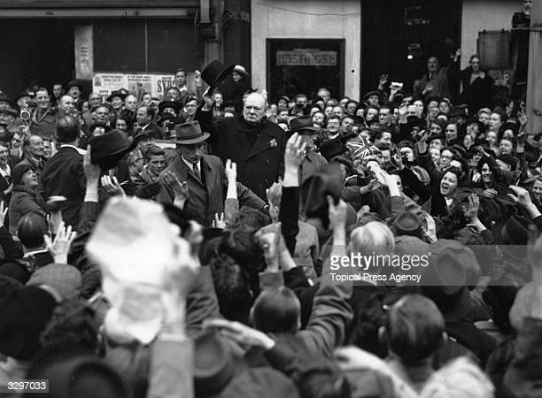 British statesman Sir Winston Leonard Spencer Churchill raises his hat to the crowd at Walham Green during his tour of London