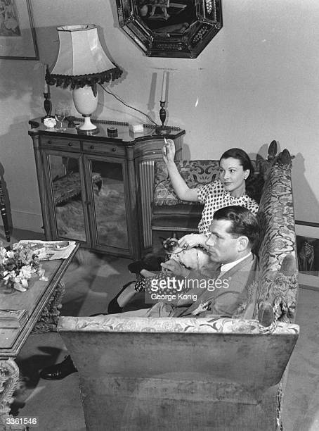 English stage and film actor Laurence Olivier and Vivien Leigh relaxing at their Chelsea home with 'Mew' the cat