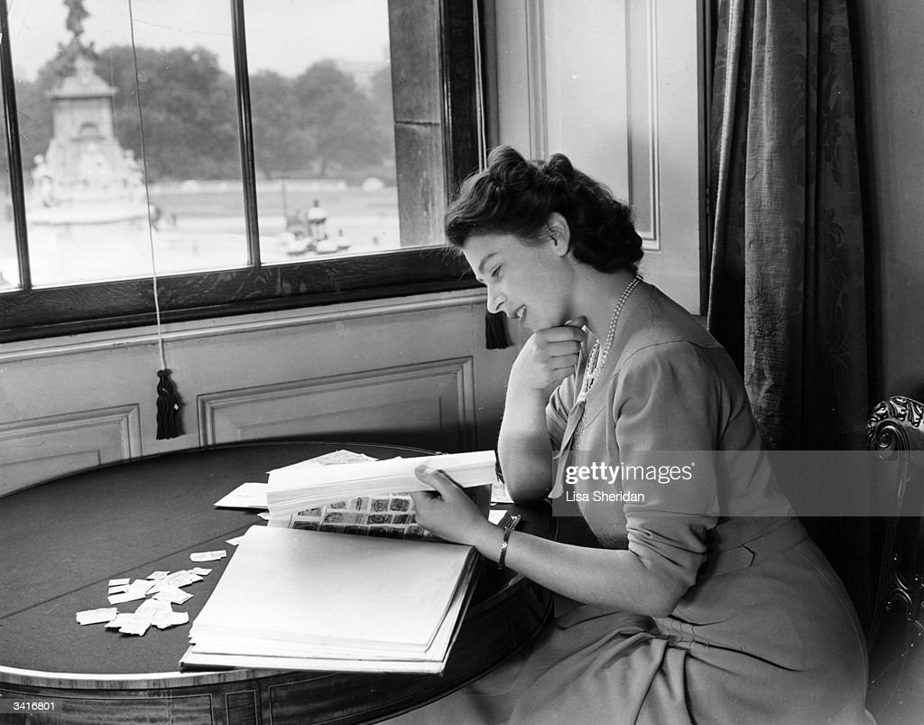 Princess Elizabeth looking through her stamp collection in the State Apartments at Buckingham Palace.