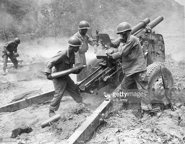 Three American soldiers of a US artillery gun crew loading a howitzer during the Korean war