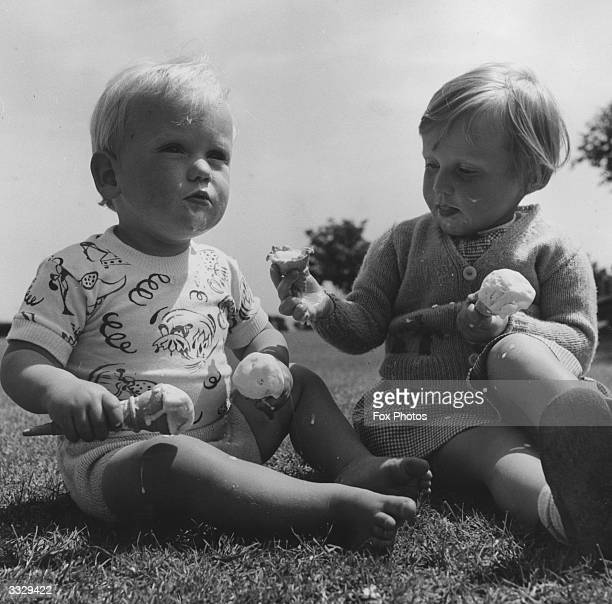 Two toddlers sit on a green together holding two melting ice cream cones each both have ice cream on their clothes and faces