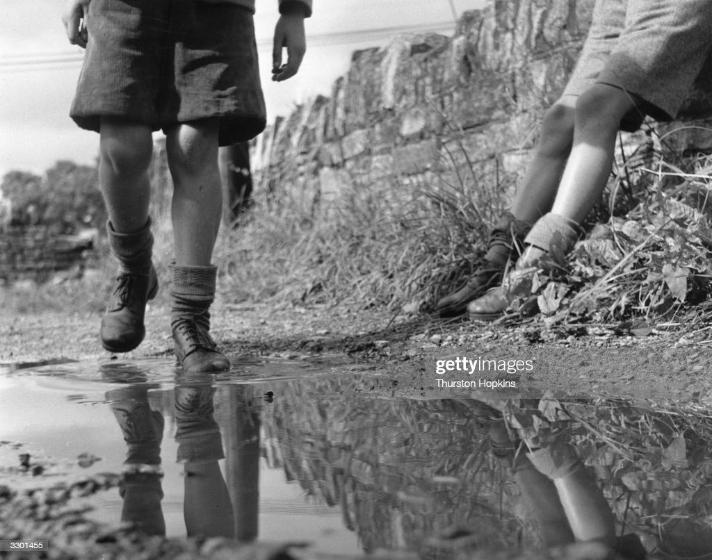 A young boy walking through a puddle on a country lane near Street in Somerset. Original Publication: Picture Post - 7884 - Children's Shoes - unpub.