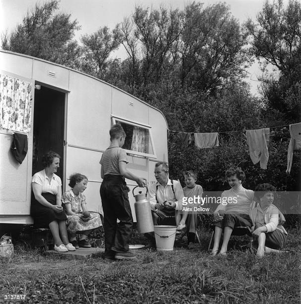 Father is peeling potatoes watched by the rest of the Grogan family They are outside their caravan during a holiday near Blackpool Lancashire in...