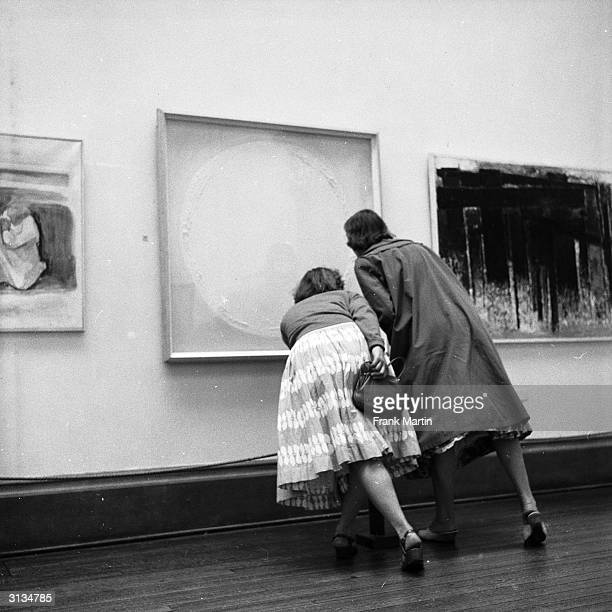 Visitors examine a painting at an exhibition of modern art organised by the Contemporary Art Society on the theme of religion in London's Tate...