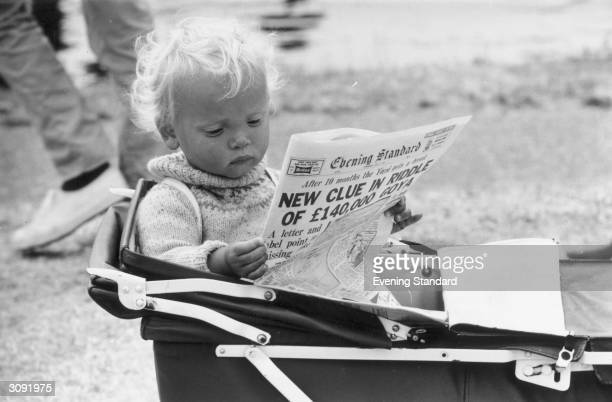 Young Roy Turner at Henley regatta prefers to read the paper in his pram