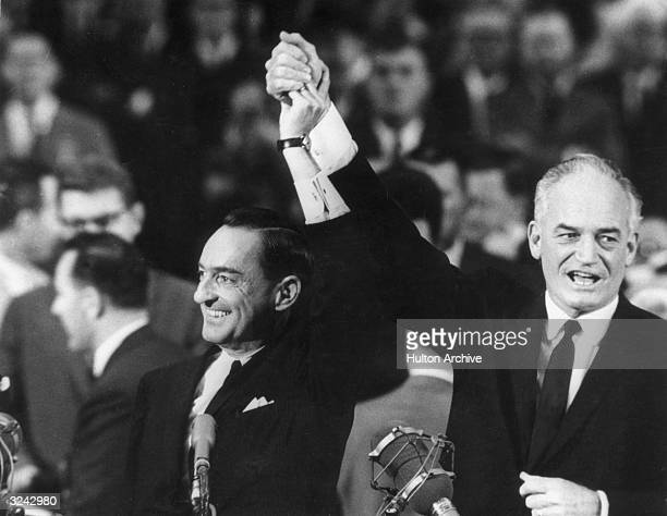 United States senator and Republican presidential candidate Barry Goldwater stands and raises his hand with his running mate William Miller at the...