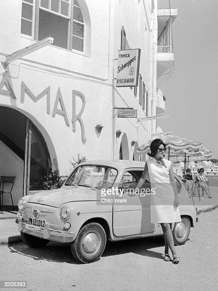 A woman leaning on a Fiat 850 parked outside a post office in Mallorca