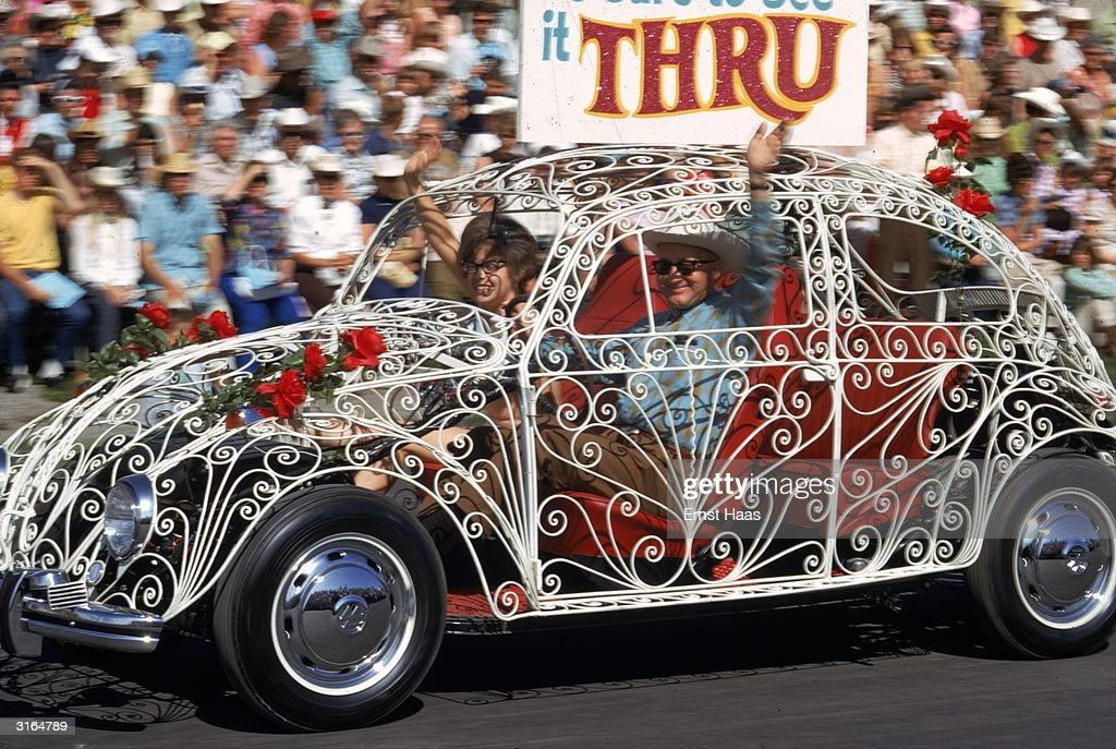 A Volkswagen Beetle with bodywork made of white wrought iron in a parade in new York City.
