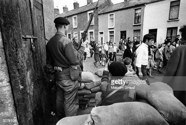 Marchers on a civil rights demonstration in Belfast pass by an armed British Army sentry point
