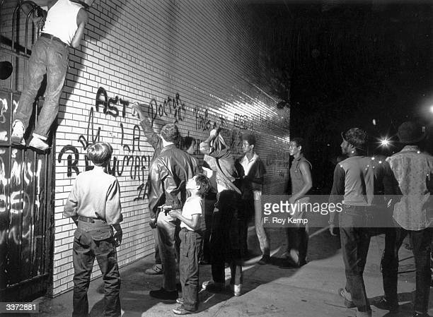 A group of youths spraypaint graffiti on a New York wall