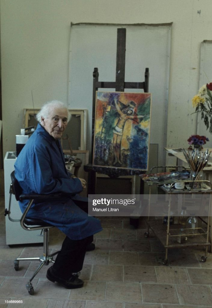 July 1973, the painter <a gi-track='captionPersonalityLinkClicked' href=/galleries/search?phrase=Marc+Chagall&family=editorial&specificpeople=214176 ng-click='$event.stopPropagation()'>Marc Chagall</a> at his home in Saint-Paul de Vence, on the occasion of the inauguration of the Musee National Message Bible which is devoted to Nice. Dressed in his blue blouse, he poses in front of a painting of Christ that he painted for the museum.