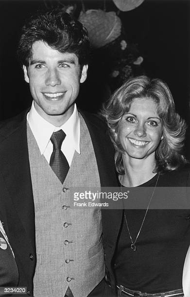 American actor John Travolta smiles as he poses with Australian singer and actor Olivia NewtonJohn at a party for director Randal Kleiser's film...