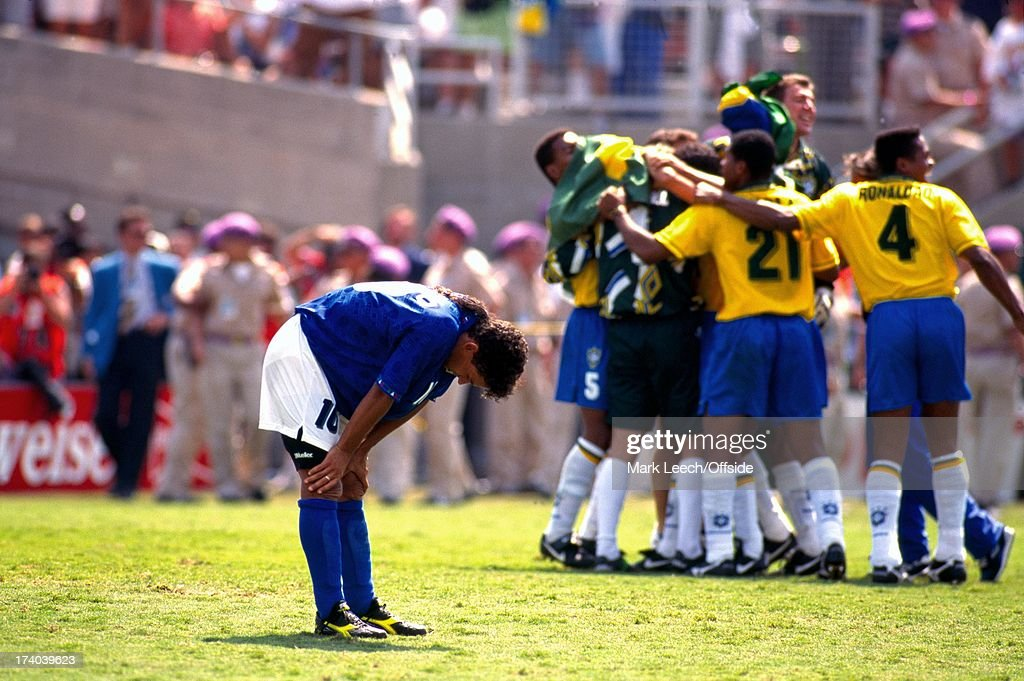 17 July 1994 World Cup Final 1994, Brazil v Italy - Los Angeles, Roberto Baggio has his hands on his knees in despair as the Brazilian team celebrate his missed penalty which won them the world cup.