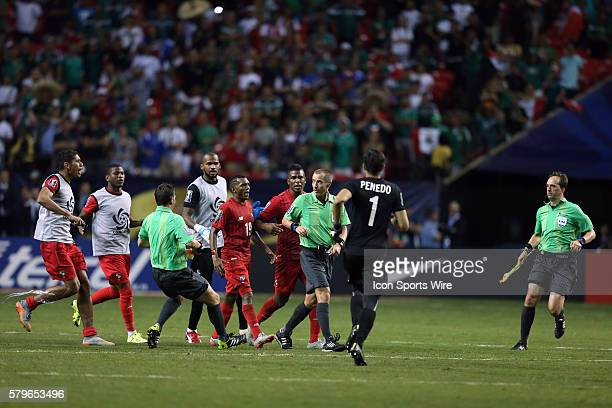 At the end of the game Alberto Quintero and Harold Cummings confront Referee Mark Geiger as Jaime Penedo and Assistant Referees Philippe Briere and...