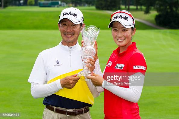 Chella Choi of South Korea and her father and caddie Ji Yeon Choipose with the crystal glass trophy after Choi won her first tournament in a playoff...