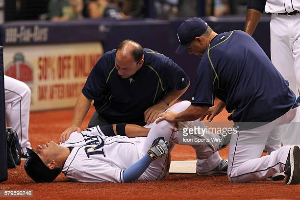 Tampa Bay Rays shortstop Asdrubal Cabrera is checked on by Tampa Bay Rays manager Kevin Cash and the Rays trainer afer injuring himself rounding...